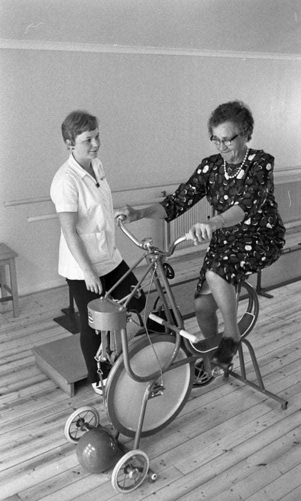 4143853d8215 Loka brunn 22 juli 1966 En äldre dam i knäkort klänning cyklar på en  motionscykel under överinseende av en arbetsklädd tränare på kurorten Loka  brunn.