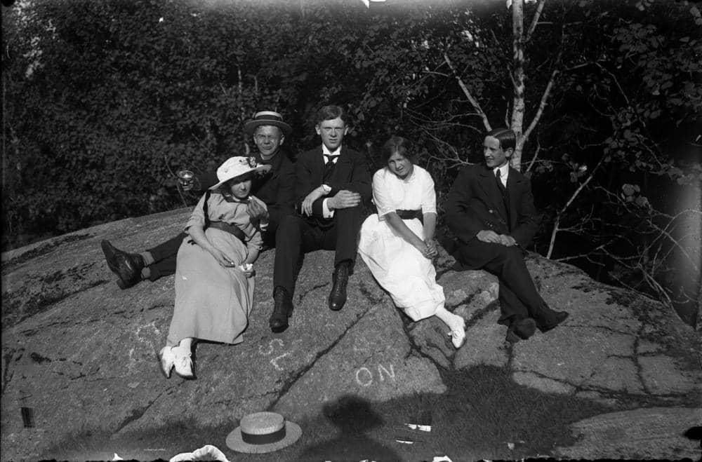 Två unga kvinnor och tre män på en sten.